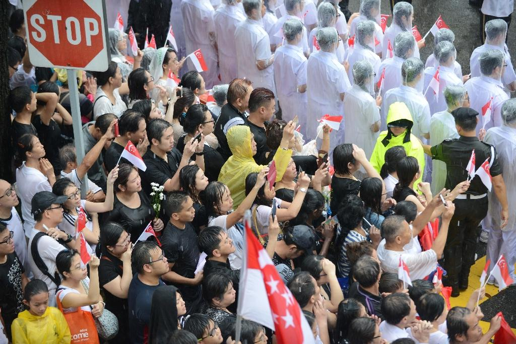 Members of the public wait outside Parliament House for the state funeral procession of Singapore's former prime minister Lee Kuan Yew in Singapore on March 29, 2015