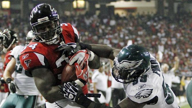 Atlanta Falcons fullback Ovie Mughelli (34) scores despite the defense of Philadelphia Eagles outside linebacker Moise Fokou (53) in the second half of an NFL football game at the Georgia Dome in Atlanta on Sunday, Sept. 18, 2011. (AP Photo/Butch Dill)