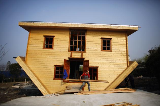 A labourer works at an upside-down house under construction at Fengjing Ancient Town