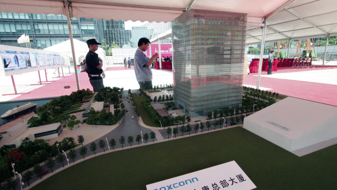FILE-In this Thursday, May 10, 2012, file photo, Chinese men walk near a scale model of the Shanghai headquarters for the Foxconn Technology Group displayed at the groundbreaking ceremony in Shanghai, China. The company that makes Apple's iPhones suspended production at a factory in China on Monday, Sept. 24, 2012, after a brawl by as many as 2,000 employees at a dormitory injured 40 people.  The fight, the cause of which was under investigation, erupted Sunday night at a privately managed dormitory near a Foxconn Technology Group factory in the northern city of Taiyuan, the company and Chinese police said. (AP Photo/File)