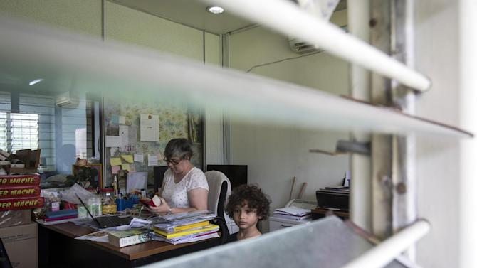 Jacquita Gomes, 53, left, accompanied by her grandson, Raphael Ariano, 4, checks her mobile phone at her office in Kuala Lumpur, Malaysia on Thursday, July 30, 2015. Gomes is torn about whether to believe that plane debris found more than 16 months after the mysterious disappearance of Malaysia Airlines Flight 370 is the first concrete evidence that her husband is truly gone. (AP Photo/Joshua Paul)