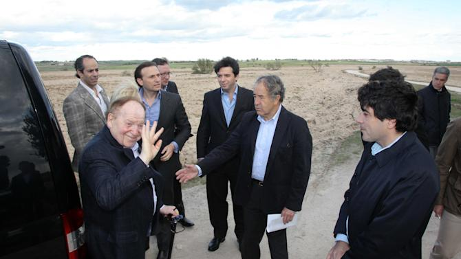 """In this photo released by the Madrid Regional Government on May 6,  2012,  CEO of Las Vegas Sands Corp. Sheldon Adelson, left in foreground, waves while visiting Alcorcon, which was one of the possible sites for the EuroVegas project on the outskirts of Madrid, with others unidentified.  It is announced Sept. 7, 2012, casino giant Las Vegas Sands Corp. has chosen Madrid over Barcelona for a multi-billion dollar gambling resort project dubbed """"EuroVegas"""".  With Supporters point out the prospects of construction jobs and service casino jobs will bring improvement to the high jobless rate and shrinking economy in Spain, but critics predict that gambling will attract criminals. (AP Photo/Comunidad de Madrid)"""