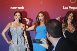 A man uses phone to take picture of Vergara posing with wax likenesses of herself during unveiling at Madame Tussauds wax museum in New York