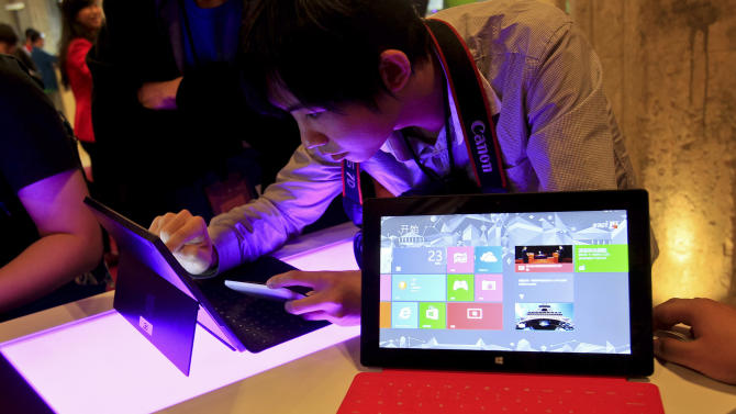 FILE - In this Tuesday Oct. 23, 2012, file photo, a Chinese man tries out the new Surface tablet computer made by Microsoft at a show in Shanghai ahead of the launch of the operating system on Oct. 26. With the release of Windows 8, PC makers are doing their best to blur the boundaries between the PC and tablet with an array of devices that mash keyboards and touch screens together in different ways. (AP Photo) CHINA OUT