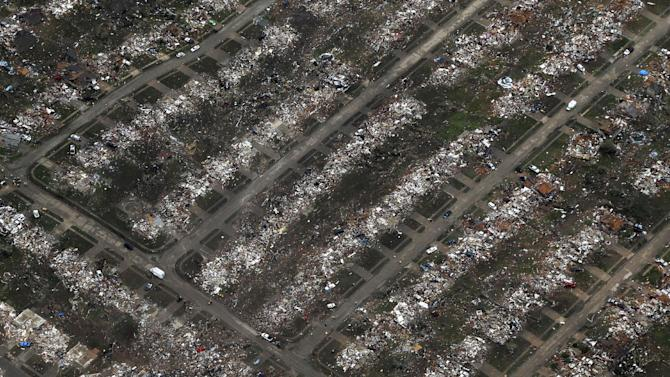 An aerial view of an entire neighborhood destroyed by Monday's tornado is shown Tuesday, May 21, 2013, in Moore, Okla. A huge tornado roared through the Oklahoma City suburb Monday, flattening  entire neighborhoods and destroying an elementary school with a direct blow as children and teachers huddled against winds. (AP Photo/Tony Gutierrez)