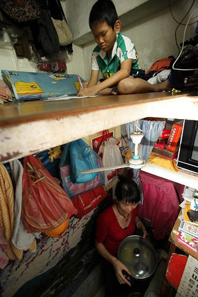 The son does homework in the loft while Wang Xuanna cooks below.