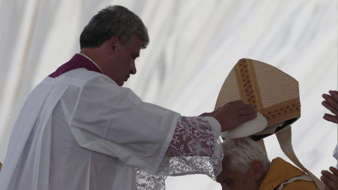 Pope Benedict XVI is helped by a prelate to wear his miter as he celebrates a Mass at the Cuatro Vientos airport during the Catholic Church's World Youth Day celebrations, in Madrid, Sunday, Aug. 21, 2011. (AP Photo/Gregorio Borgia)