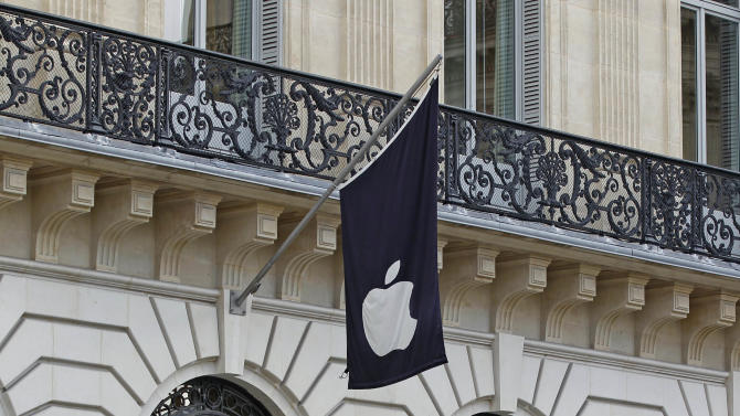People look into an Apple store located near the Paris Opera, Tuesday, Jan. 1, 2013. A robbery took place at the flagship store on Monday, a few hours after the close of business. (AP Photo/Remy de la Mauviniere)