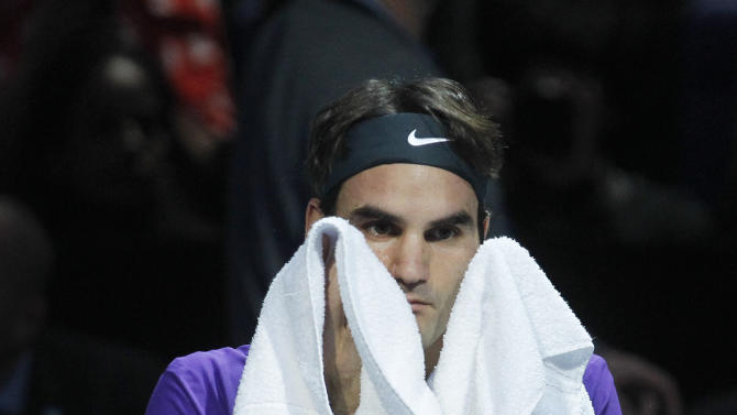 Roger Federer of Switzerland wipes his face with a towel during a break as he plays  Novak Djokovic of Serbia during their ATP World Tour Tennis singles final match in London, Monday, Nov.  12, 2012. (AP Photo/Sang Tan)