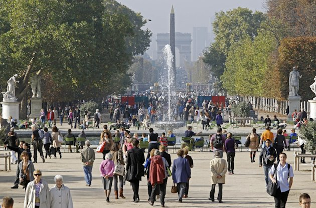 This Oct. 23, 2012 photo shows people strolling in the Tuileries gardens, with the Arc de Triomphe in background, in Paris. The 400-year-old Tuileries gardens sitting tranquilly in the heart of the capital between the Louvre Museum and the Place de la Concorde offers a place to relax with their ornate fountains, magical statues and fresh air. (AP Photo/Remy de la Mauviniere)