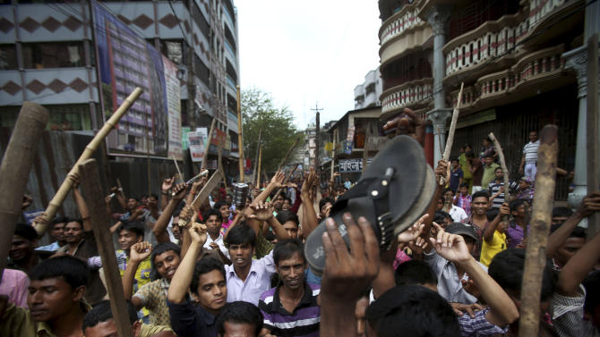 """Protestors march down the street, demanding the death penalty for those responsible for the April 24 collapse of a garment factory building that killed hundreds in Savar, near, Dhaka, Bangladesh, Tuesday, April 30, 2013. A top Bangladesh court on Tuesday ordered the government to """"immediately"""" confiscate the property of a collapsed building's owner, as thousands of protesters demanding death penalty for the man clashed with police, leaving 100 people injured. (AP Photo/Wong Maye-E)"""