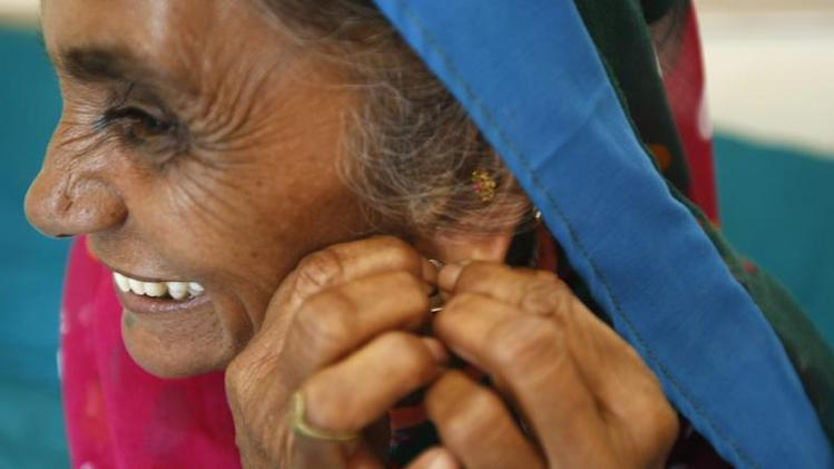 Farmer Kolipatle wears a silver ring before trying a gold earring inside a jewellery shop at Vadnagar village in Gujarat