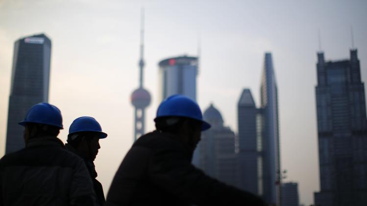 Construction workers stand on a street corner at the financial district of Pudong in Shanghai