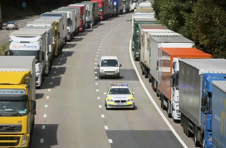 A police car passes lorries parked on the M20 motorway as park of Operation Stack in southern England