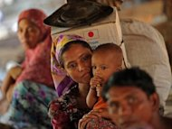 "A Muslim Rohingya woman carries her baby inside the Bawdupha camp for internally displaced people on the outskirts of Sittwe, capital of Myanmar's western Rakhine state. Food, water and medical help are in short supply at overcrowded camps in violence-hit western Myanmar that are ""stretched beyond capacity"", the UN refugee agency said Tuesday"