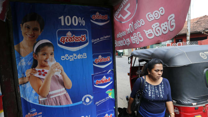 A Sri Lankan woman walks past an advertisement of a Fonterra product in Colombo, Sri Lanka, Tuesday, Aug. 6, 2013. Fonterra, the world's largest dairy exporter, announced Saturday that hundreds of tons of infant formula, sports drinks and other products sold in seven countries could be tainted. On Tuesday, Sri Lanka's health ministry said it had ordered all milk products imported from New Zealand be stopped at ports and the withdrawal of products with whey protein from supermarkets as a precaution after reports of contamination that could cause botulism. (AP Photo/Eranga Jayawardena)