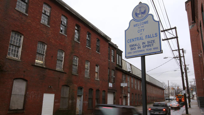 In this Thursday, Jan. 12, 2012 photo, cars pass a welcome sign at an entrance to Central Falls, R.I. The state of Rhode Island stepped in to take over financially struggling Central Falls in 2010, with a state-appointed receiver filing for bankruptcy on behalf of the city in August 2011. (AP Photo/Steven Senne)