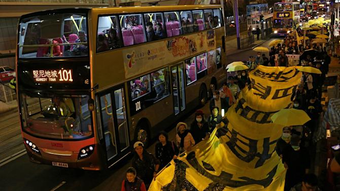 Protesters carry a long banner, with the words 'I want real universal suffrage' in Chinese, and yellow umbrellas - the recent symbol of Hong Kong's democracy movement - during a march to mark Christmas Eve, on December 24, 2014