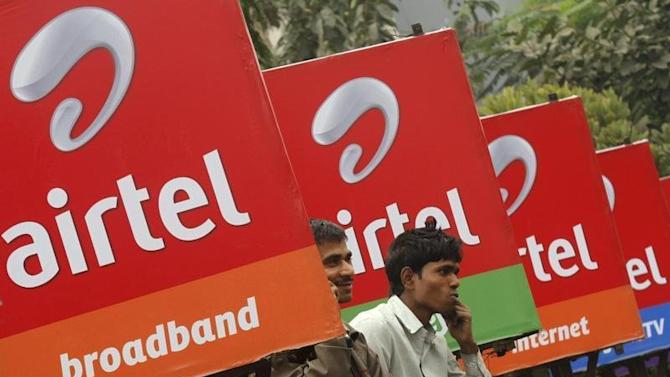 Men make phone calls as they sit on a railing with Bharti Airtel billboards installed on it, along a sidewalk in Kolkata
