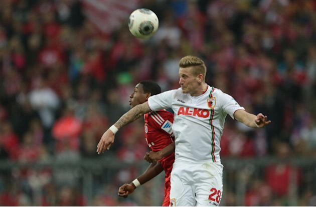 Bayern's David Alaba of Austria, background left, and Augsburg's Andre Hahn challenge for the ball during the German first division Bundesliga soccer match between FC Bayern Munich and FC Augsburg, in