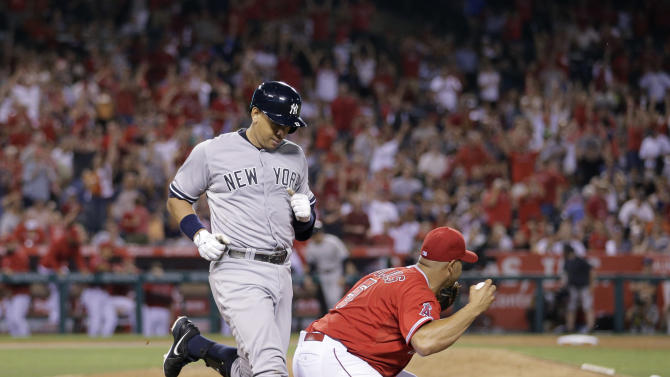 Los Angeles Angels first baseman Albert Pujols, right, celebrates after getting the final out of the game, against New York Yankees' Alex Rodriguez, in a baseball game Tuesday, June 30, 2015, in Anaheim, Calif. The Angels won 2-1. (AP Photo/Jae C. Hong)