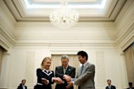 South Korean Foreign Minister Kim Sung-hwan (C), US Secretary of State Hillary Clinton (L) and Japanese Foreign Minister Koichiro Gemba (R) shake hands at the Peace Palace in Phnom Penh on July 12. Clinton Friday urged Southeast Asian nations to promote workers&#39; rights and improve labour conditions as a means of spurring economic growth