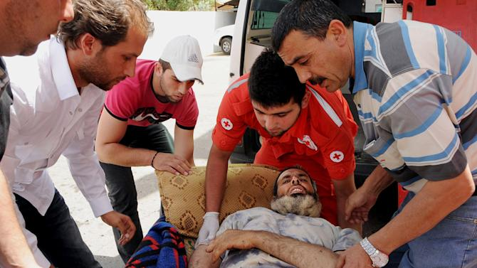 FILE - In this Saturday, June 8, 2013 file photo, members of the Lebanese Red Cross carry a Syrian man who was wounded in Qusair, during battles between the rebels and Syrian government forces, is rushed to a hospital in the Bekaa Valley, east of Beirut, Lebanon. Syrian rebels' defeat in Qusair cost them more than a strategic location, it has also left a battered spirit and deep frustration. Over the course of a year, rebels holding the town had heavily fortified it with tunnels, mine fields, and booby traps and when the regime assault came they fought back ferociously. But in the end they were outgunned and outnumbered, and were forced into a harrowing, crushing flight from the town. (AP Photo, File)