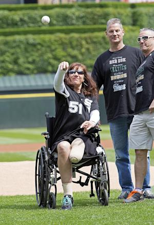 Karen Rand, who lost part of her leg in the Boston Marathon bomb blasts, throws out the ceremonial first pitch before a baseball game between the Chicago White Sox and the Oakland Athletics, Saturday, June 8, 2013. (AP Photo/Charles Cherney)