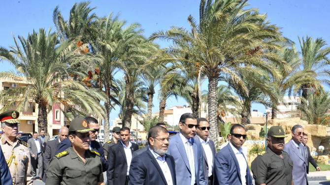 In this photo released by the Egyptian Presidency, President Mohammed Morsi, center, walks with officials during a visit to el-Arish, Egypt, Friday, Oct. 5, 2012.(AP Photo/Egyptian Presidency)
