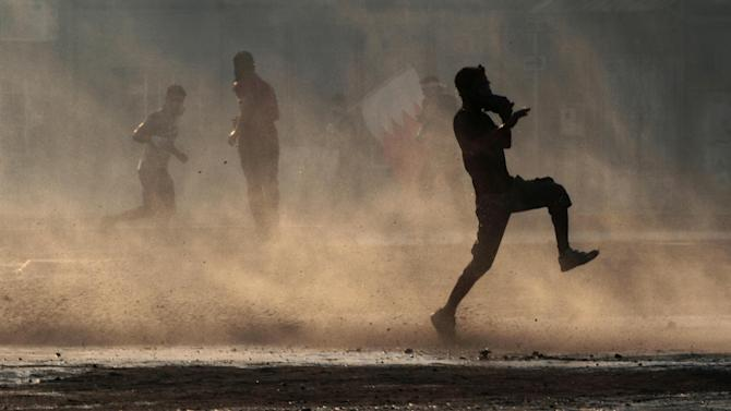Bahraini anti-government protesters, some with national flags, run from tear gas and the spray of water cannons during clashes with riot police in Sanabis, Bahrain, on Friday, Oct. 5, 2012. Riot police dispersed hundreds of anti-government protesters trying to reach a heavily guarded site that was once the hub of their uprising. (AP Photo/Hasan Jamali)