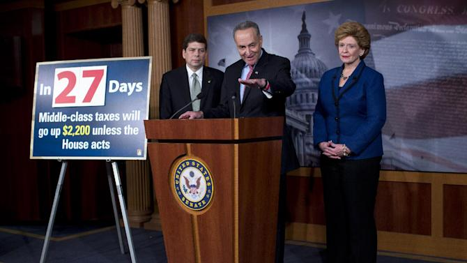 Sen. Charles Schumer, D-N.Y., center, accompanied by Sen. Debbie Stabenow, D-Mich., right, and Sen. Mark Begich, D-Alaska, gestures during a news conference on Capitol Hill in Washington, Wednesday, Dec. 5, 2012, to talk about the debate on tax rates and the fiscal cliff.  (AP Photo/ Evan Vucci)