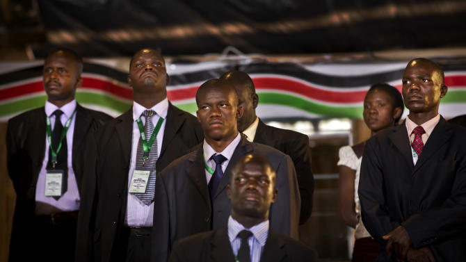 Security and bodyguards of the election commission chairman stand as he delivers a statement to the media, at the National Election Center in Nairobi, Kenya Friday, March 8, 2013. Kenya's drawn-out race for president was coming down to the wire on Friday, with the leading candidate hovering right at the 50 percent mark needed to avoid a runoff with his top challenger. (AP Photo/Ben Curtis)