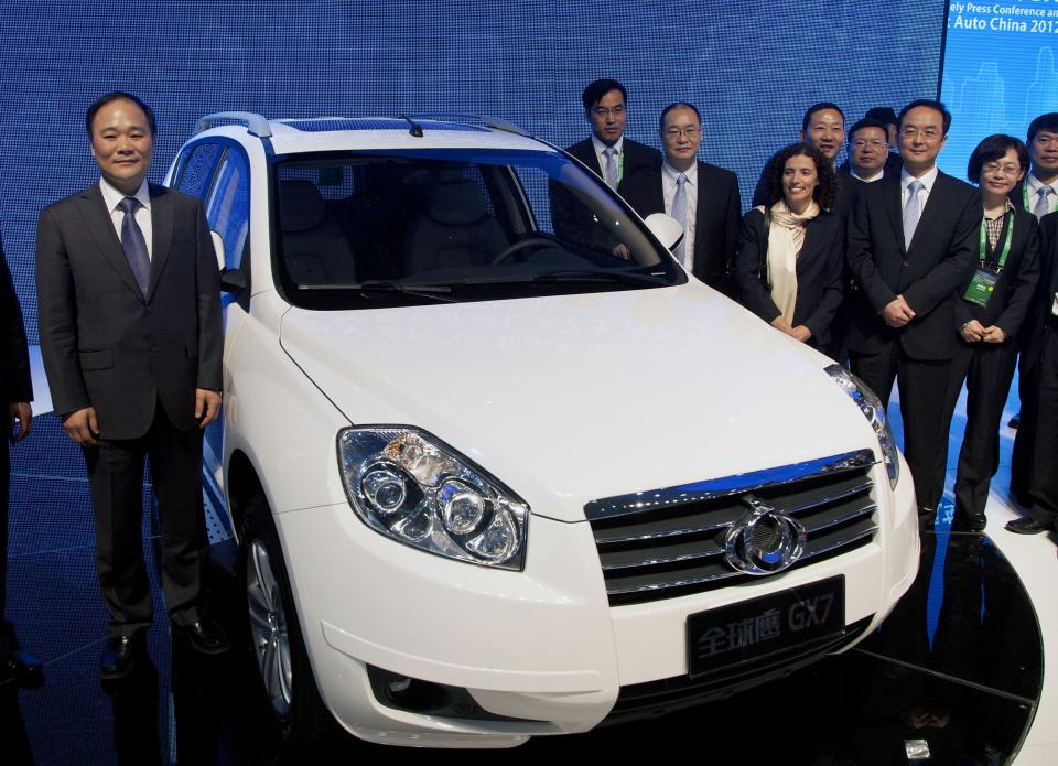 Geely Holding Group Chairman Li Shufu, left, stands next to the new Geely Gleagle GX7 model after it was unveiled at the Beijing International Automotive Exhibition in Beijing, China Monday, April 23, 2012. (AP Photo/Andy Wong)
