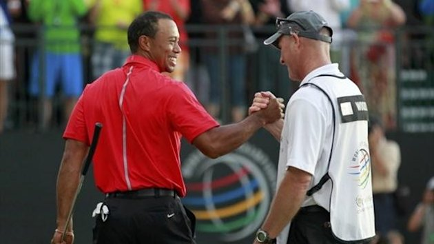 Tiger Woods celebrates with his caddie Joe LaCava after sinking his final putt on the 18th green to win the 2013 WGC-Cadillac Championship PGA golf tournament in Doral, Florida March 10, 2013