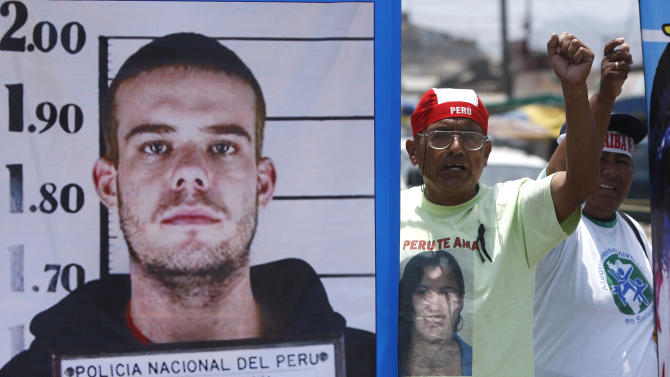People protest against Joran van der Sloot as they hold up an enlarged picture of his police mug shot outside San Pedro prison where his murder trial is held in Lima, Peru, Wednesday Jan. 11, 2012. Van der Sloot pleaded guilty on Wednesday to the 2010 murder of a 21-year-old Peruvian woman he met at a Lima casino who was killed five years to the day of the unsolved disappearance in Aruba of an American teen in which he remains the main suspect. (AP Photo/Karel Navarro)