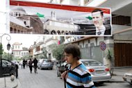 A man walks under a banner depicting Syrian President Bashar al-Assad as he crosses a road in old Damascus on April 30. The Syrian authorities have set a deadline of 15 days for people who had committed &quot;unlawful acts&quot; to give themselves up, as a wave of arrests was reported across the country