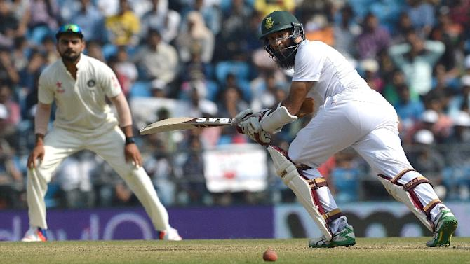 India's captain Virat Kohli (L) looks on as South Africa's captain Hashim Amla plays a shot on the third day of their third Test match, at The Vidarbha Cricket Association Stadium in Nagpur, on November 27, 2015