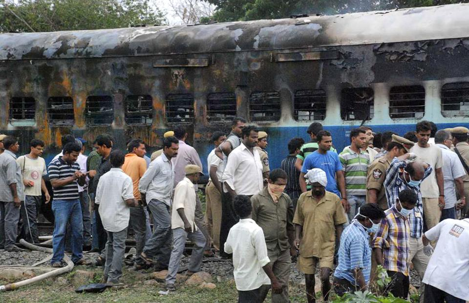 Railway workers and officials inspect the burnt coach of a passenger train at Nellor nearly 500 kilometers (310 miles) south of Hyderabad, India, July 30, 2012. A fire engulfed a passenger car on a moving train in southern India on Monday, killing at least 47 people, officials said.  (AP Photo)