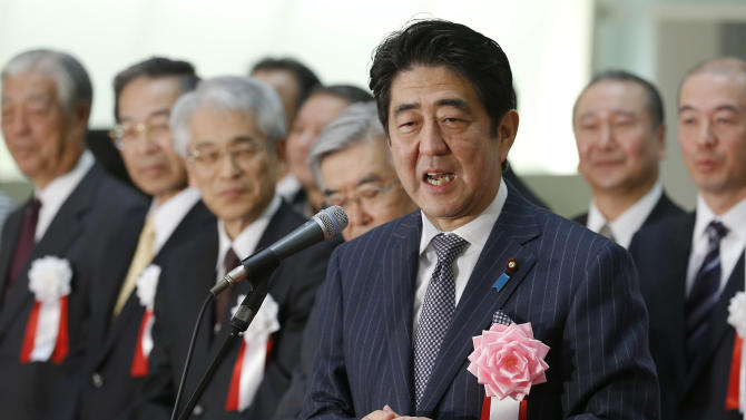 """Japanese Prime Minister Shinzo Abe speaks during a ceremony to wrap up the year's trading on the Tokyo Stock Exchange in Tokyo Monday, Dec. 30, 2013. """"Thanks to our efforts, the economy went from minus to positive,"""" Abe said. With winter bonuses up by several hundred dollars on average, he said, """"You have to use that money, keep it moving."""" Asian shares advanced Monday in light but upbeat pre-holiday trading, as Japan's Nikkei 225 index ended 2013 at its highest level in over six years. (AP Photo/Shizuo Kambayashi)"""