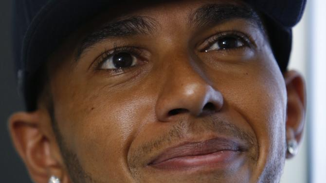 Mercedes Formula One driver Lewis Hamilton of Britain smiles during an interview after a publicity event to unveil watches that he and teammate Nico Rosberg of Germany co-designed in Singapore