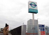 The sign for east London&#39;s Abbey Road Station is seen against the backdrop of apartment buildings on Friday, Nov. 10, 2012. Abbey Road Station is more than nine miles from the striped crosswalk made famous by the Beatles album Abbey Road, but this drab transit hub keeps drawing confused fans of the Fab Four into unwanted jaunts through a gritty, industrial area of east London. (AP Photo/Raphael Satter)