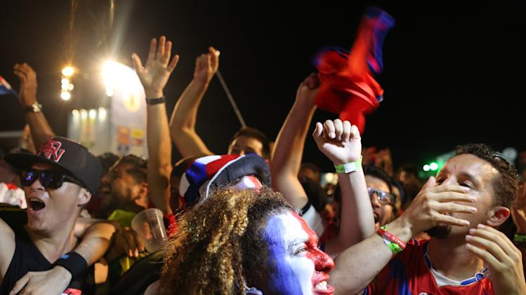 Costa Rica soccer fans celebrate a goal against Greece as they watch the World Cup round of 16 match on a live telecast inside the FIFA Fan Fest area on Copacabana beach in Rio de Janeiro, Brazil, Sunday, June 29, 2014. (AP Photo/Leo Correa)