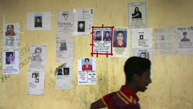 A boy runs past a school turned make-shift morgue with portraits of missing persons, mostly workers at the garment factory building which collapsed, plastered over its walls on Monday April 29, 2013 in in Savar, near Dhaka, Bangladesh. Rescue workers in Bangladesh gave up hopes of finding any more survivors in the remains of the building that collapsed five days ago, and began using heavy machinery on Monday to dislodge the rubble and look for bodies - mostly of workers in garment factories there. At least 381 people were killed when the illegally constructed, 8-story Rana Plaza collapsed in a heap on Wednesday morning along with thousands of workers in the five garment factories in the building.(AP Photo/Wong Maye-E)