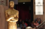 People look at an Oscar statue during preparations for the 85th Academy Awards in Hollywood, California February 23, 2013. REUTERS/Mario Anzuoni