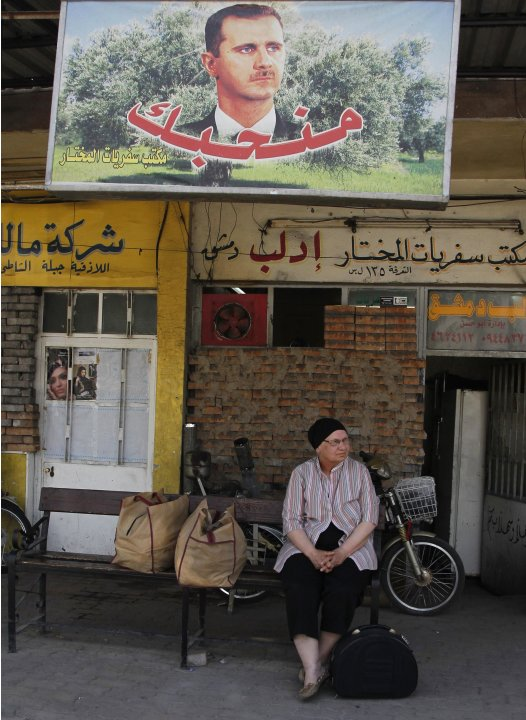 A woman waits for bus at al-Abassin bus station near Damascus' Jobar neighbourhood