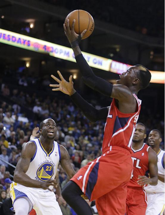 Atlanta Hawks' Dennis Schroder, right, lays up a shot in front of Golden State Warriors' Draymond Green (23) during the first half of an NBA basketball game Friday, March 7, 2014, in Oakland,