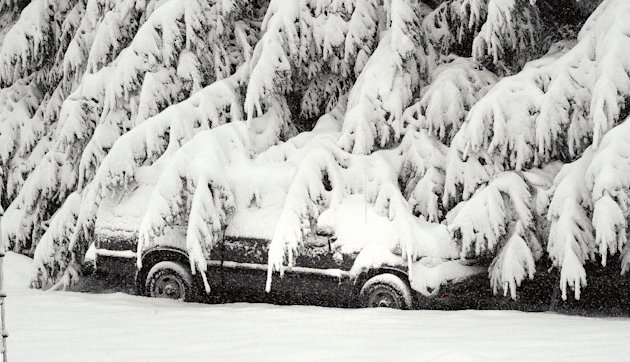 A lone parked car is draped with snow covered branches south of Morgantown, W.Va. from a snowfall on Tuesday, Oct. 30, 2012. West Virginia&#39;s death toll climbed to at least six and hundreds of thousands remained without power Wednesday, Oct. 31, from the wet, heavy snow that superstorm Sandy dumped on the mountains, snapping trees, pulling down power lines and collapsing homes. (AP Photo/The Dominion-Post, Ron Rittenhouse)