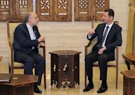 A picture released by the Syrian Arab News Agency shows Syrian President Bashar al-Assad (R) meeting with Iranian Foreign Minister Ali Akbar Salehi in Damascus. Syrian rebels seized a crossing on the Turkish border Wednesday even as they quit a swathe of south Damascus that activists said had been reduced to a disaster area by weeks of heavy fighting