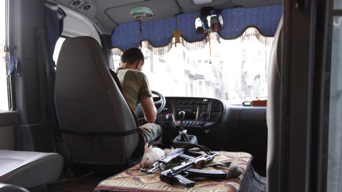 A rabbit is pictured next to weapons in a Free Syrian Army bus in Bustan Al-Basha district in Aleppo