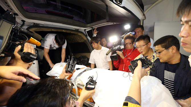Policemen transport a stretcher with a body believed to be fugitive ferry businessman Yoo Byung-un, at a hospital in Suncheon